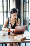 Junge Frau, die in der Kaffeestube sitzt lizenzfreie stockfotos
