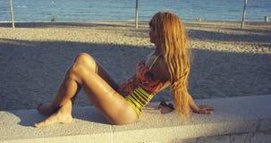 Junge Frau, die an der Küste sich entspannt Stockfotos