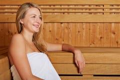Junge Frau, die in der Sauna sitzt Stockfoto