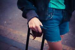 Junge Frau, die in der Straße mit einem Koffer steht Lizenzfreies Stockfoto