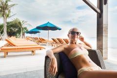 Junge Frau, die an der Strandbar sich entspannt stockfoto
