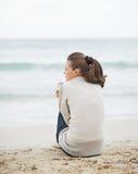 Junge Frau, die in der Strickjacke beim Sitzen auf einsamem Strand einwickelt Lizenzfreie Stockbilder
