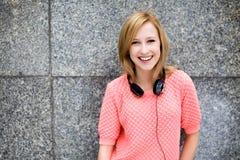 Junge Frau, die an der Wand sich lehnt Lizenzfreies Stockfoto