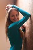 Junge Frau, die an der Wand sich lehnt Lizenzfreie Stockfotografie
