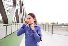 Junge Frau, die in die Stadt auf grüner Stahlbrücke läuft Stockfoto