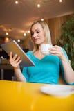 Junge Frau, die digitale Tablette beim Halten der Kaffeetasse verwendet stockfotos