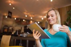 Junge Frau, die digitale Tablette beim Halten der Schale verwendet lizenzfreie stockfotografie