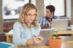 Junge Frau, die digitale Tablette im kreativen Büro verwendet Lizenzfreies Stockfoto