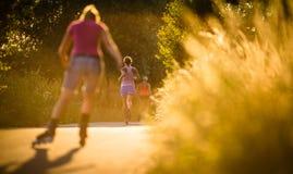 Junge Frau, die draußen auf ein reizenden sonnigen Sommer evenis läuft stockbilder