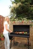 Junge Frau, die draußen auf einem Grill kocht Stockbild