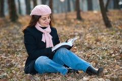 Junge Frau, die draußen ein Buch liest stockfoto