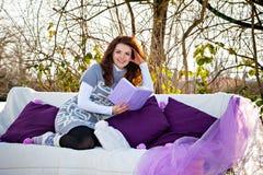 Junge Frau, die draußen ein Buch liest Stockbild