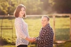 Junge Frau, die draußen eine Großmutter umarmt stockbilder