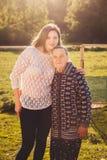 Junge Frau, die draußen eine Großmutter umarmt lizenzfreie stockfotografie