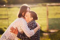 Junge Frau, die draußen eine Großmutter umarmt Stockbild