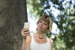 Junge Frau, die draußen Foto oder selfie mit dem Ca des Handys nimmt Lizenzfreie Stockfotos