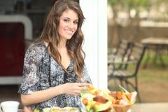 Junge Frau, die draußen frühstückt stockfotos