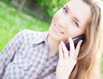 Junge Frau, die draußen Handy verwendet Stockfoto