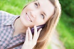 Junge Frau, die draußen Handy verwendet Lizenzfreies Stockbild