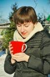 Junge Frau, die draußen heißen Tee trinkt Stockfoto