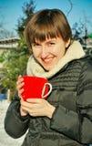 Junge Frau, die draußen heißen Tee trinkt Lizenzfreies Stockfoto