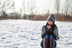 Junge Frau, die draußen im Winter und in trinkendem Tee sitzt Lizenzfreie Stockfotografie