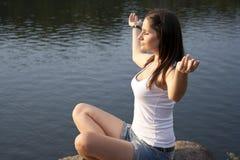 Junge Frau, die draußen Meditation tut Stockfotografie