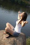 Junge Frau, die draußen Meditation tut Stockbild