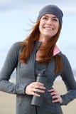 Junge Frau, die draußen mit Wasserflasche lächelt Lizenzfreie Stockfotos