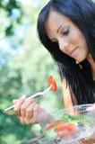 Junge Frau, die draußen Salat isst Stockfotos