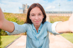 Junge Frau, die draußen selfie mit Handy in Paris nimmt Lizenzfreie Stockfotos