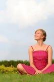 Junge Frau, die draußen sitzt Lizenzfreies Stockfoto