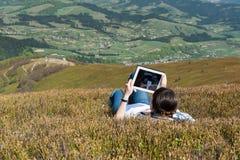 Junge Frau, die draußen Tablet-Computer verwendet Stockfotografie