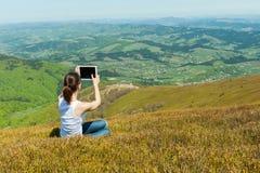 Junge Frau, die draußen Tablet-Computer verwendet Lizenzfreie Stockfotos