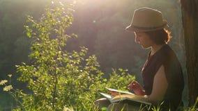 Junge Frau, die draußen unter einem Baum sitzt und mit Buch und Tablette arbeitet Ein Student, eine Geschäftsfrau stock footage