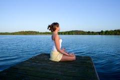 Junge Frau, die draußen Yogaübung tut stockbild