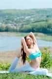 Junge Frau, die draußen Yoga auf Green River Bank tut Lizenzfreie Stockbilder
