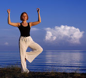 Junge Frau, die draußen Yoga tut Stockfoto