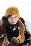 Junge Frau, die draußen heißes Getränk trinkt Stockbild