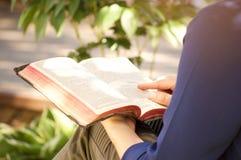 Junge Frau, die draußen heilige Bibel liest Lizenzfreie Stockfotos