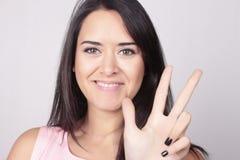 Junge Frau, die drei mit ihren Fingern zählt lizenzfreies stockbild
