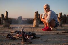 Junge Frau, die durch das Feuer an der Küste bei Sonnenuntergang sitzt lizenzfreies stockbild