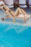 Recht junge Frau, die durch das Pool sich entspannt Stockfotos