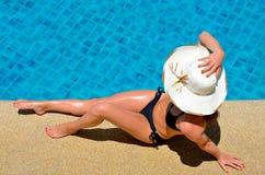 Junge Frau, die durch das Pool sich entspannt Stockbild