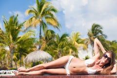 Junge Frau, die durch das tropische Pool sich entspannt lizenzfreies stockfoto