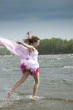Junge Frau, die durch das Wasser am Strand läuft Stockbild