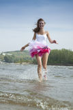 Junge Frau, die durch das Wasser am Strand läuft Stockbilder