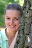 Junge Frau, die durch den Baum sich versteckt lizenzfreies stockfoto