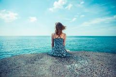 Junge Frau, die durch den Ozean sitzt Stockfotografie