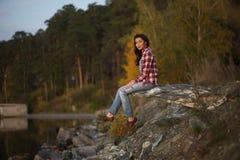 Junge Frau, die durch den See sitzt Lizenzfreies Stockbild
